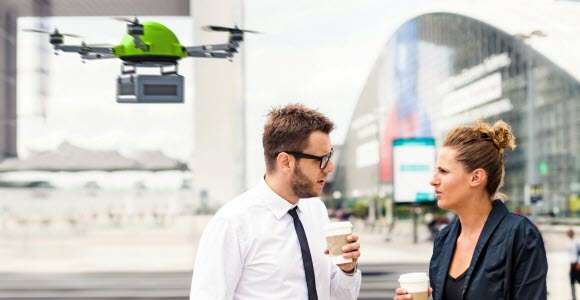 Photo: Man and woman in a discussion, a drone is circuling behind them