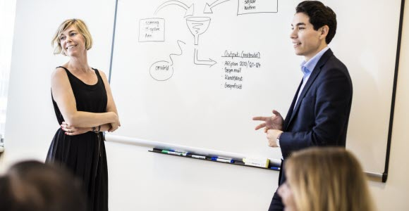 Photo: Women and man standing in front of a whiteboard