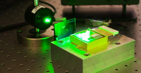 Green laser shooting through a small glass plate at a small component