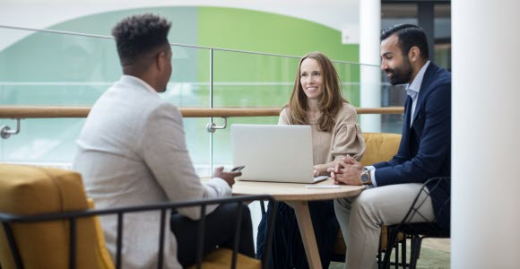 Photo: One woman and two men in a meeting in open office enviroment